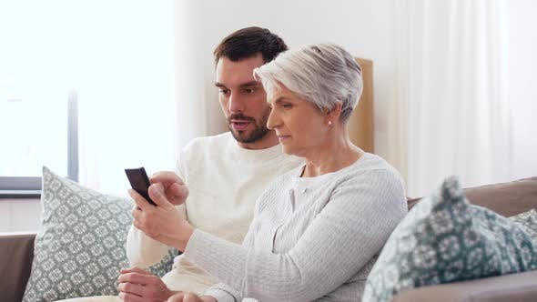 Thumbnail for Old Mother and Adult Son with Smartphone at Home