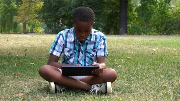 Thumbnail for A Young  Black Boy Sits on Grass in a Park and Works on a Tablet