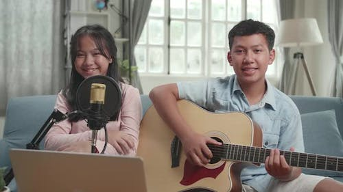Boy With Guitar And Girl Smiling. The Children Is Broadcasting Live On The Internet