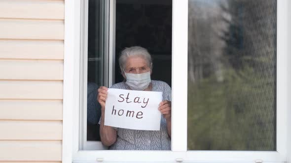 Thumbnail for Senior Woman Holds a Poster with the Words Stay Home