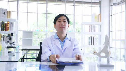 Asian Male Doctor in Lab Coat Reading and Analysing Issue in Lungs of Patient with Xray Film