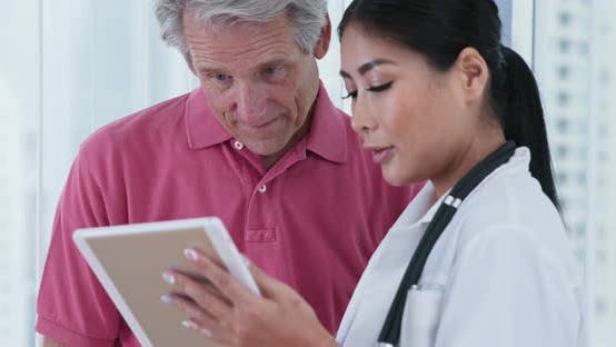 Female primary care doctor and her senior male patient discussing test results