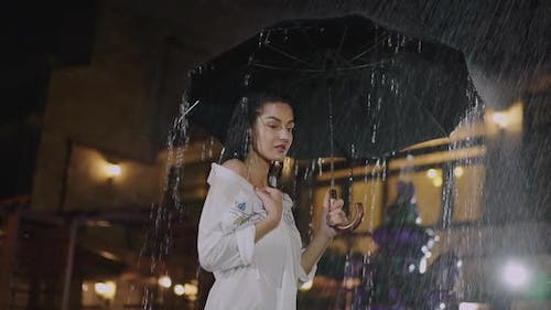 Thoughtful Brunette Stands with Umbrella and Admires Falling Fountain