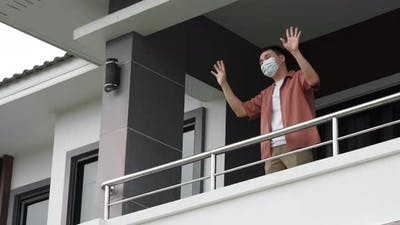quarantine man wearing a face mask and greeting neighbors from balcony of the home