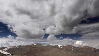 Partly Cloudy Sky Over Arid and Barren Treeless Mountain