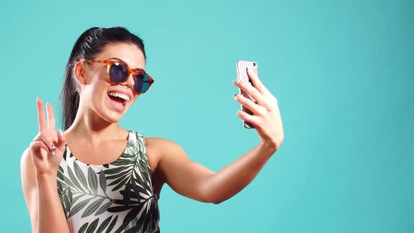 Thumbnail for Beauty Playful Brunette Woman in Dress and Glasses Posing and Making Selfie on Her Smartphone