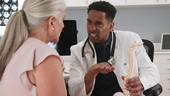 Thumbnail for Doctor and patient sitting in medical office looking at model of human spine
