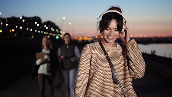 Cover Image for Young brunette woman listening to music with headphones