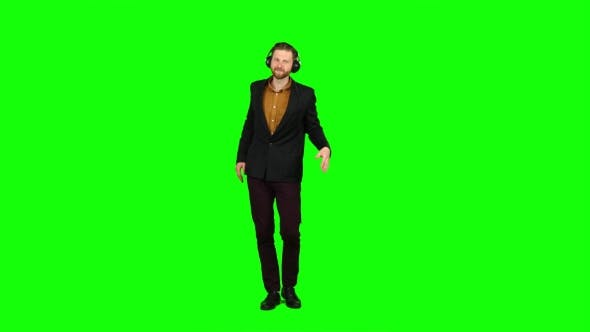 Thumbnail for Man in Headphones Listens To Music, Dances and Sings a Song. Green Screen