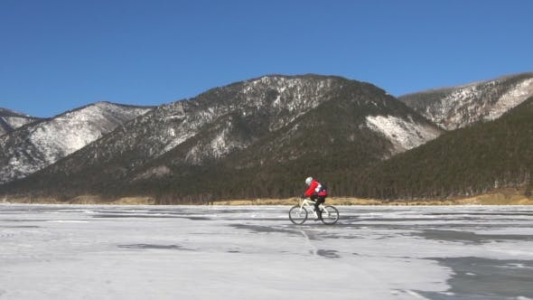 Thumbnail for Men Riding a Bicycle on the Surface of Frozen Lake