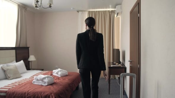 Cover Image for Young Business Woman Holding a Suitcase and Opening Door of Hotel Room