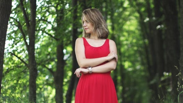 Thumbnail for Portrait of Young Woman in Red Dress on Green Bokeh Background.