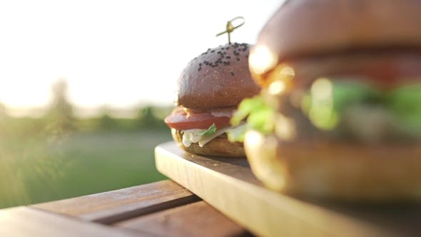 Cover Image for Hot Burgers on the Wooden Board in the Sunset Sunlight at the Coutriside, Fast Food Meals, Cooking