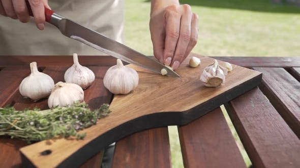 Thumbnail for The Cook Slices Garlic on the Wooden Board By Sharp Knife Outside, Cooking Outside, Cooking Healthy