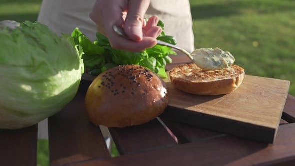 Thumbnail for The Cook Puts Sauce To the Bun and Makes Burger Outside, Countryside Cooking, Open Air Cooking, Meal