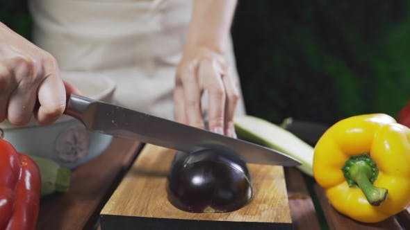 Thumbnail for The Cook Cuts the Eggplant on the Wooden Board Outside for Making Vegetarian Meal, Vegetable Cuisine