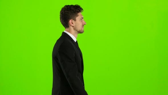 Thumbnail for Guy Walks Calmly Down the Street, He Is Happy. Green Screen