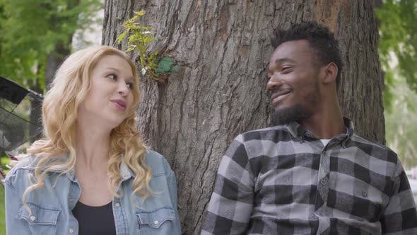 Thumbnail for Portrait Confidient Pretty Blond Woman and Handsome African American Man Talking Sitting Under an