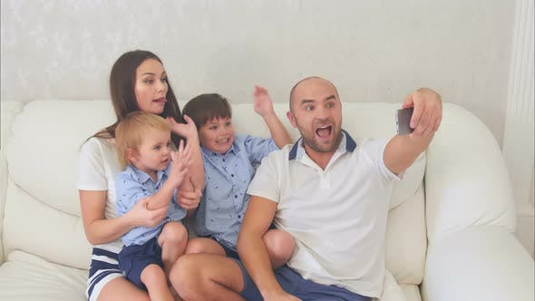 Thumbnail for Smiling Family Taking Funny Selfies Sitting on the Sofa