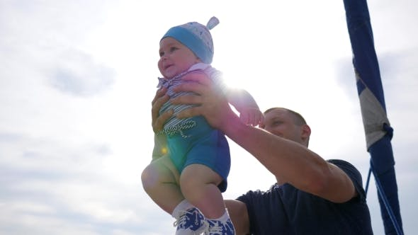 Thumbnail for Little Kid in Father's Strong Hands in Sunlight, Child Into Hands of Dad on Blue Sky Background