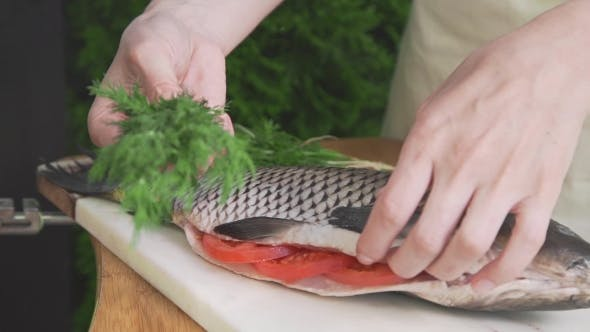 Thumbnail for Housewife Is Stuffing Raw Fish with Fennel, Carp Fish on the Board, Cooking Fish Meals Outdoors