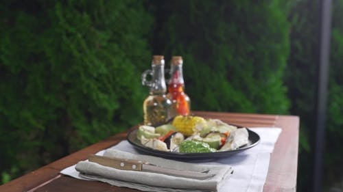 Grilled Vegetables with Fish and Pesto Sauce Are Served on the Table Outdoors, Grill and Barbecue