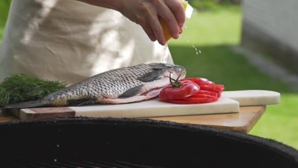 Thumbnail for Raw Carp Is Sprinkling with Lemon Juice in Front of the Fire of Grill, Preparations for the Barbecue