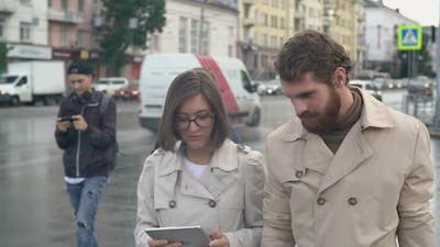 Young Man and Woman Looking at Tablet on Zebra Crossing