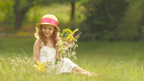 Thumbnail for Child Holds a Bouquet of Wildflowers in Her Hands, She Smells Them and Smiles