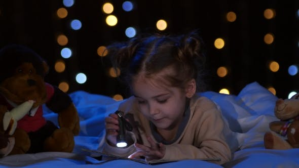 Thumbnail for Little Girl at Night Reading a Book on the Bed. Bokeh Background
