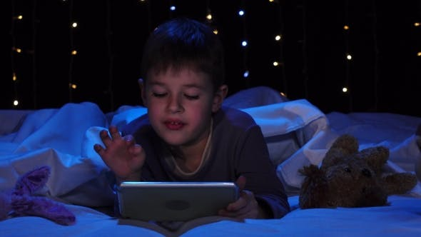 Thumbnail for Little Boy Is Lying on a Bed Holding a Laptop and Watching a Cartoon. Bokeh Background