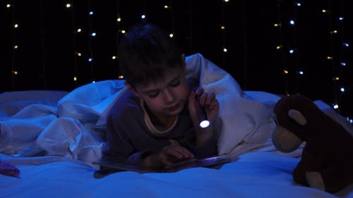 Child at Night Reading a Book on the Bed. Bokeh Background