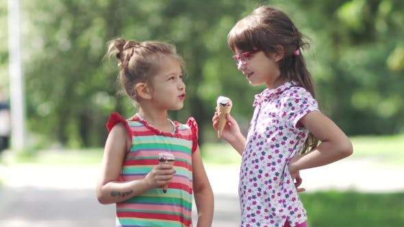 Thumbnail for Carefree Children Eat Ice Cream in Summer Park. Two Little Girls Having Fun Talking and Smiling