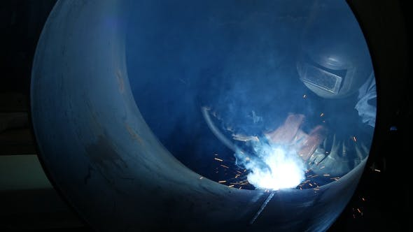 Thumbnail for Welder Inside A Big Pipe Welding The Seam To Create One Continuous Section Of Pipe