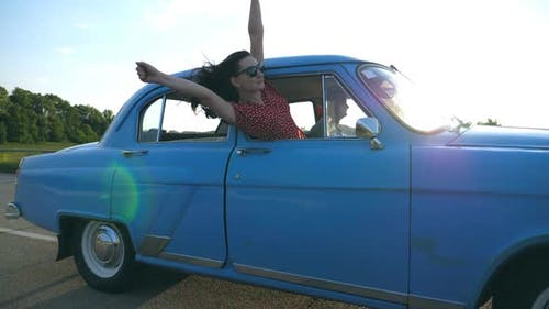 Attractive Girl in Sunglasses Leaning Out of Vintage Car Window and Enjoying Trip