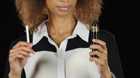 Thumbnail for Girl Holds an Ordinary Cigarette in One Hand and an Electronic Cigarette in the Other. Black