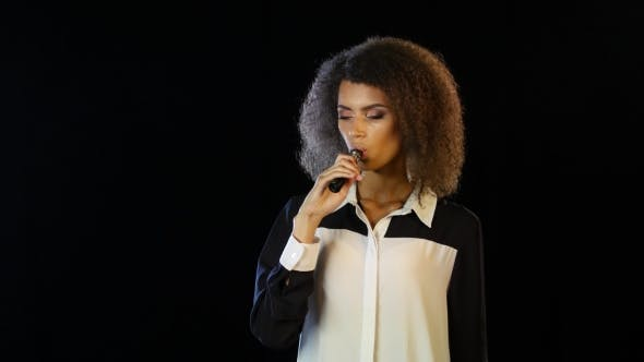 Thumbnail for Woman Is Standing in a Dark Room Smoking an Electronic Cigarette. Black Background