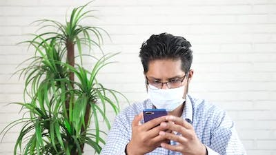 Young Man in Face Mask Using Smart Phone