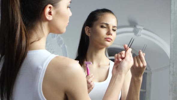 Thumbnail for Girl Holds a Pair of Tweezers and a Razor, and Chooses What To Do with Epilation