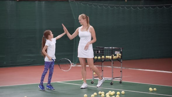 Thumbnail for Trainer Woman Giving High Five To Little Girl on Tennis Court