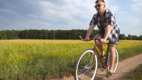 Sporty Guy in Sunglasses Cycling Along Country Trail Outdoor. Young Smiling Man Riding Vintage