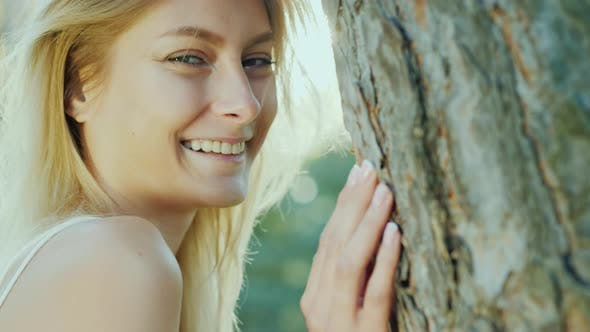 Beautiful Young Woman Stands Near a Tree, Portrait