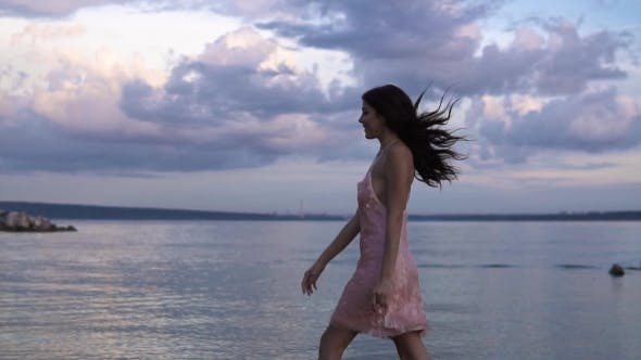 Thumbnail for Girl in Cocktail Dress Carefree Walks on the Beach at Sunset
