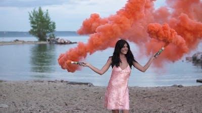 Young Woman at Sunset Waving Red Smoke Bombs