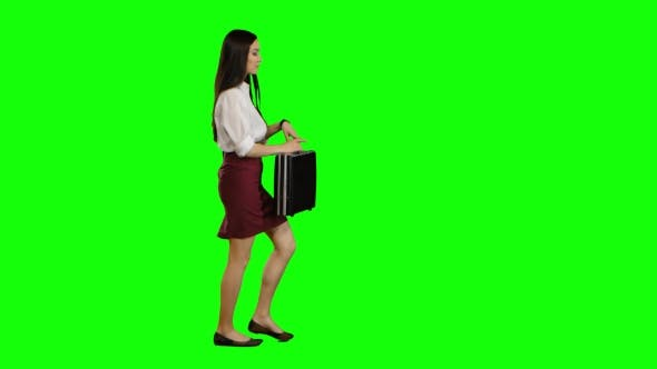Thumbnail for Girl Hurries To Important Negotiations, in Her Hand a Diplomat with Documents. Green Screen