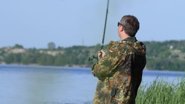 Thumbnail for Fishing Lover Holds a Rod in His Hand and Twists the Reel Throws a Fishing Rod