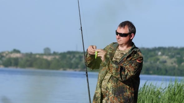 Thumbnail for Man Clings a Bait To a Fishing Rod, He Wants To Catch Fish