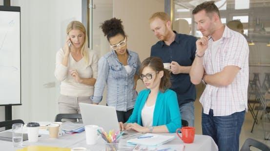 Thumbnail for Frau mit Kollegen beobachten Laptop
