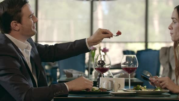 Thumbnail for Handsome Man Feeding Woman at Romantic Dinner. Couple Dining at Romantic Date
