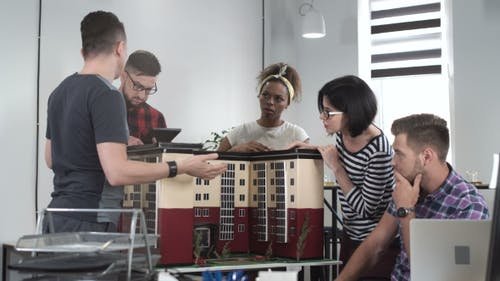 Co-workers Discussing By Miniature of Building